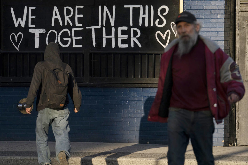 Two men walk past a sign on Main Street in downtown Vancouver, B.C., Monday, April 5, 2021. THE CANADIAN PRESS/Jonathan Hayward