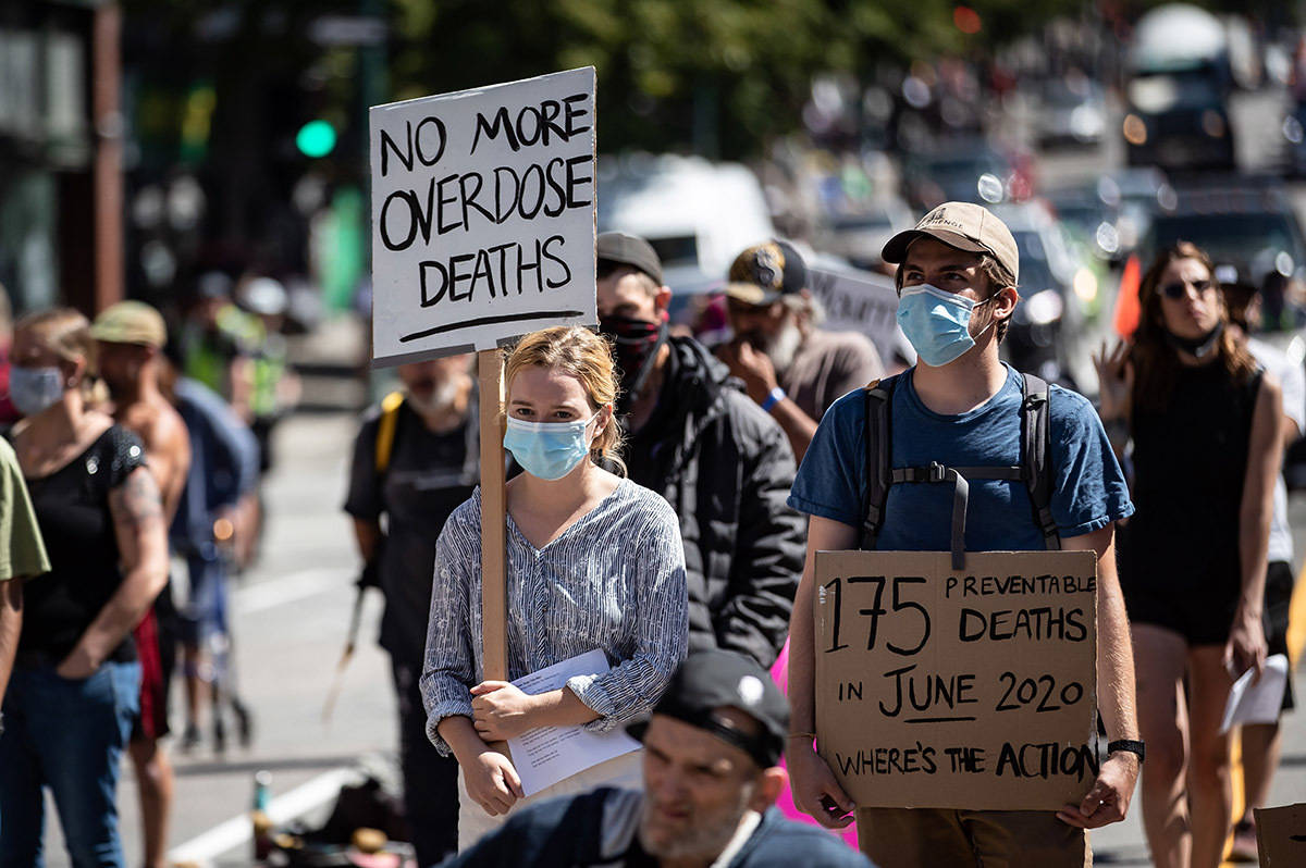 FILE – People hold signs during a memorial march to remember victims of overdose deaths in Vancouver on Saturday, August 15, 2020. THE CANADIAN PRESS/Darryl Dyck