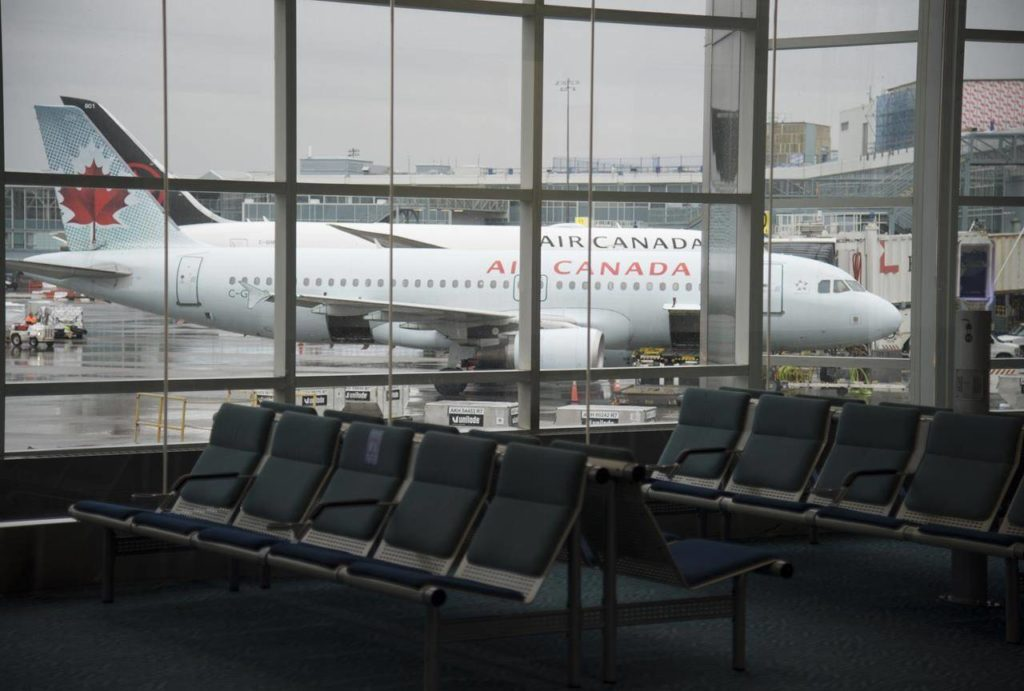A plane is seen through the window on the tarmac of Vancouver International Airport as the waiting room is empty Tuesday, June 9, 2020. Canadians are awaiting details on Air Canada's plans for ticket refunds after the airline reached a deal for $5.9B in federal aid. THE CANADIAN PRESS/Jonathan Hayward