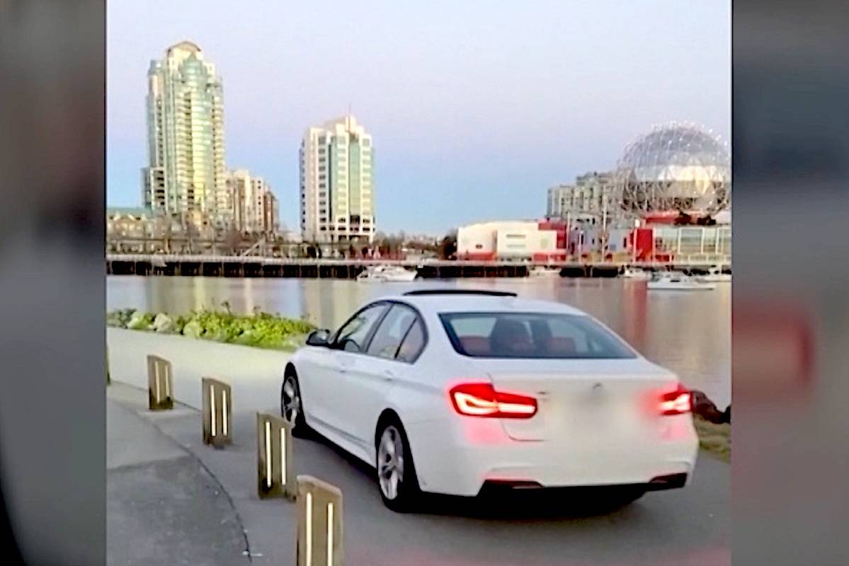 Video captured Wednesday, April 14, shows a white BMW driving along the seawall between Vancouver's Plaza of Nations and Science World. (Krimda Toravantian/Screen grab)