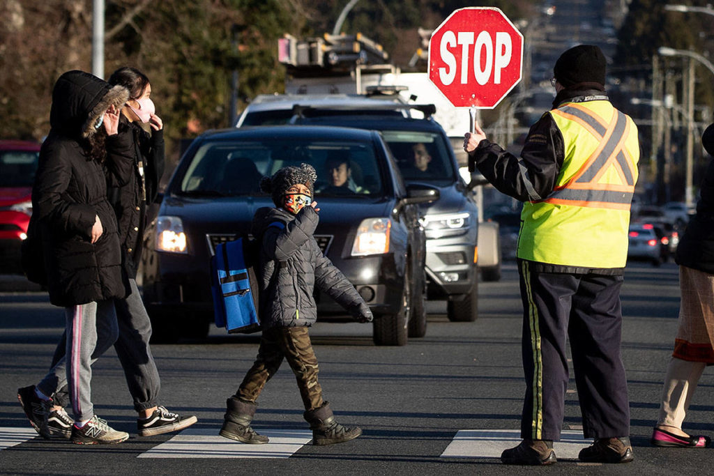 A crossing guard stops traffic as students wearing face masks to curb the spread of COVID-19 arrive at Ecole Woodward Hill Elementary School, in Surrey, B.C., on Tuesday, February 23, 2021. A number of schools in the Fraser Health region, including Woodward Hill, have reported cases of the B.1.7.7 COVID-19 variant first detected in the U.K. THE CANADIAN PRESS/Darryl Dyck