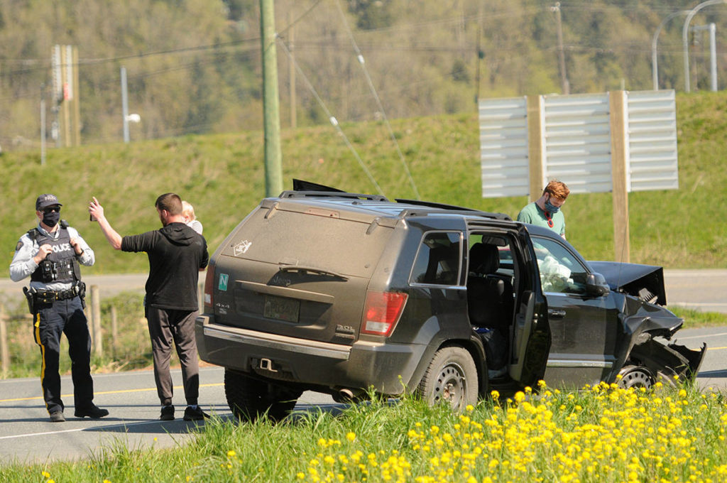 A man holds a child while speaking with RCMP following an erratic driving incident on Highway 1 in Chilliwack on Friday, April 16, 2021. The child and a woman (but not this man) were in this Jeep Grand Cherokee which hit a barrier and a parked car on Highway 1 and continued driving. The vehicle finally exited the highway at Yale Road West and came to a stop. (Jenna Hauck/ Chilliwack Progress)