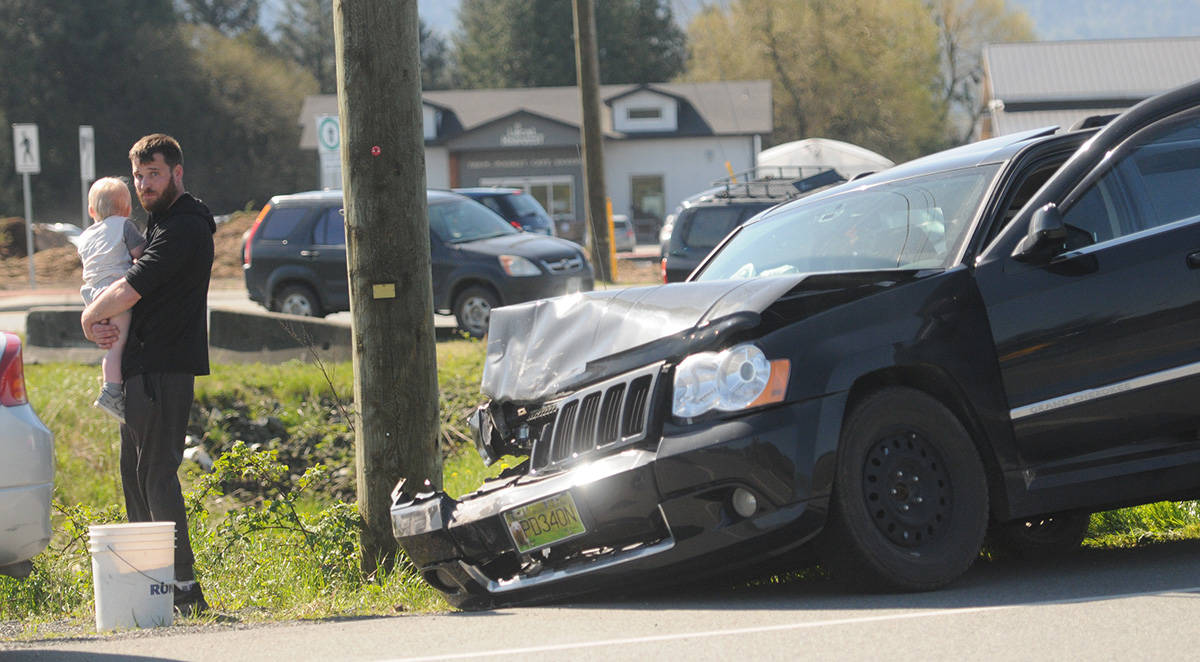 A man holds a child following an erratic driving incident on Highway 1 in Chilliwack on Friday, April 16, 2021. The child and a woman (but not this man) were in this Jeep Grand Cherokee which hit a barrier and a parked car on Highway 1 and continued driving. The vehicle finally exited the highway at Yale Road West and came to a stop. (Jenna Hauck/ Chilliwack Progress)