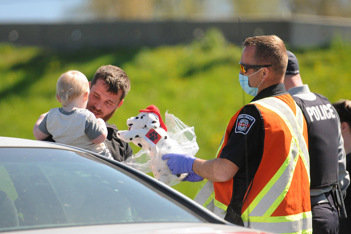 A member of the Chilliwack Fire Department hands a child a stuffed Dalmatian toy following an erratic driving incident on Highway 1 on Friday, April 16, 2021. (Jenna Hauck/ Chilliwack Progress)