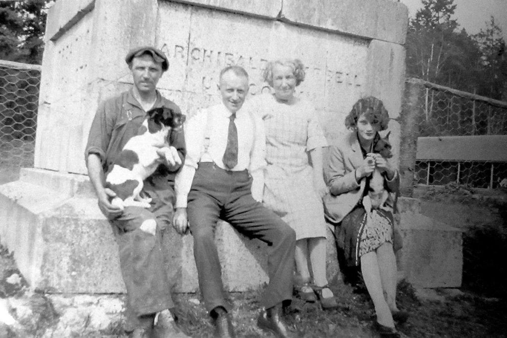 Pansy May Stuttard (centre) with friends at the Treaty of Washington monument on the Tsawwassen/Point Roberts border in the 1920s - with part of her infamous 16-room Goat Ranch lodge in the background. Contributed photo