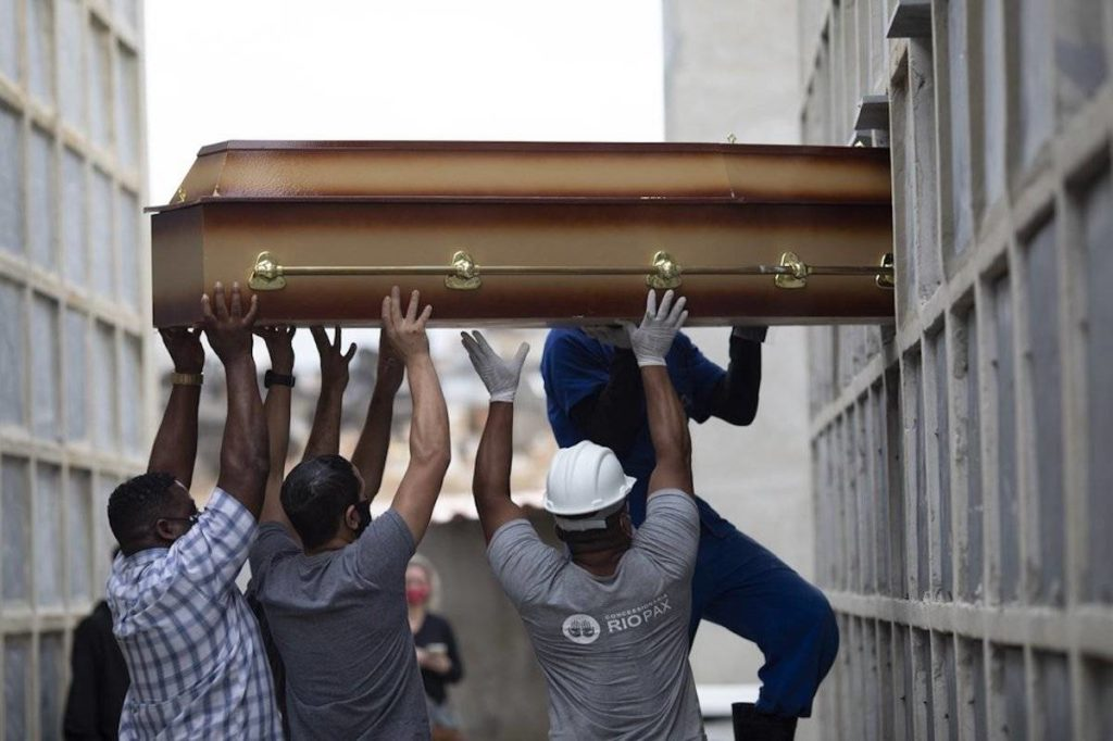 The remains of a woman who died from complications related to COVID-19 are placed into a niche by cemetery workers and relatives at the Inahuma cemetery in Rio de Janeiro, Brazil. (AP Photo/Silvia Izquierdo) FILE - In this April 13, 2021, file photo, the remains of a woman who died from complications related to COVID-19 are placed into a niche by cemetery workers and relatives at the Inahuma cemetery in Rio de Janeiro, Brazil. The global death toll from the coronavirus topped a staggering 3 million people Saturday, April 17, 2021, amid repeated setbacks in the worldwide vaccination campaign and a deepening crisis in places such as Brazil, India and France. (AP Photo/Silvia Izquierdo, File)