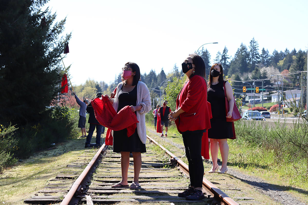 Stz'uminus councillor Shawna Seymour holds a red dress beside Chief Roxanne Harris and Ladysmith councillor Amanda Jacobson. (Cole Schisler photo)