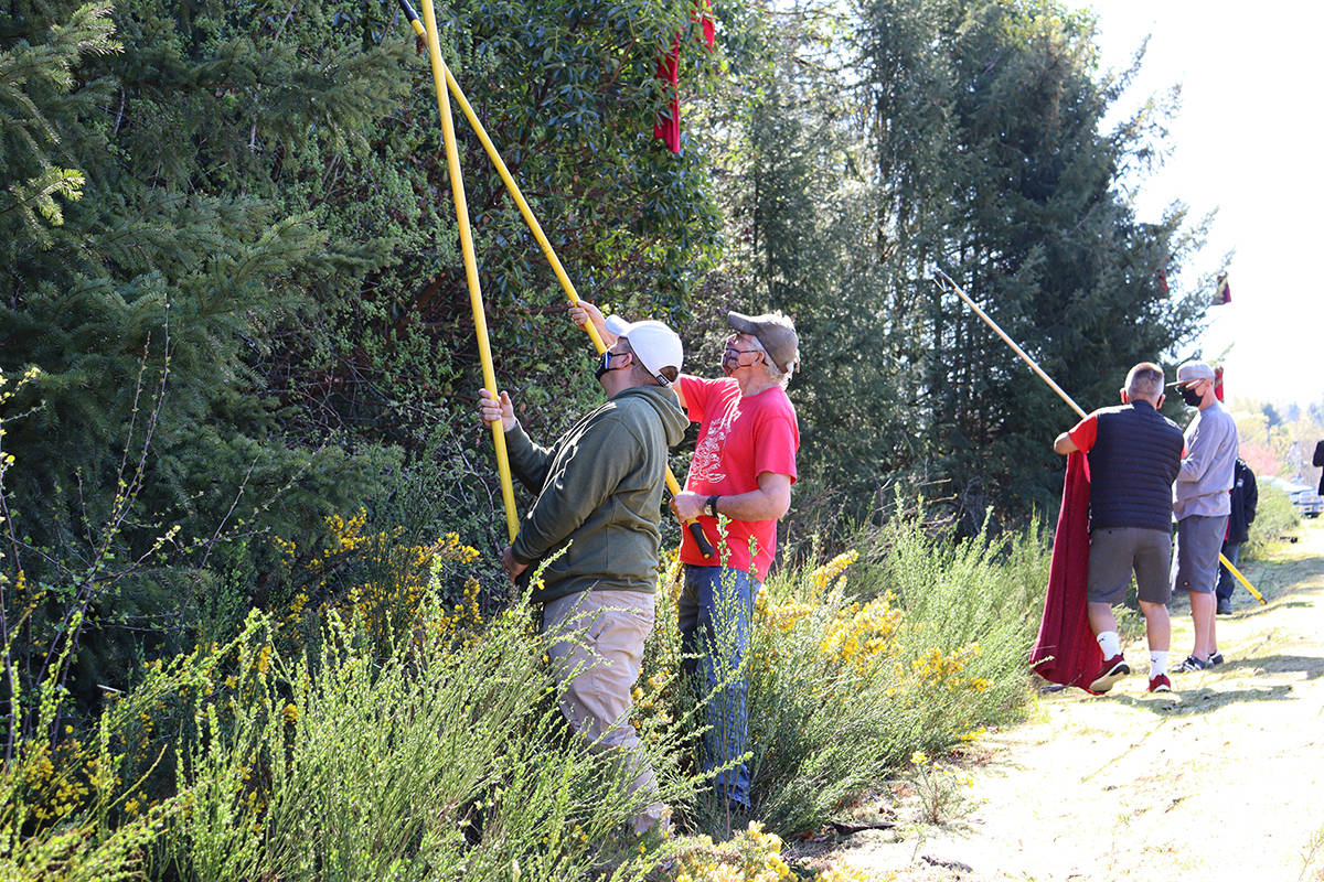 Stz'uminus councillor Tim Harris and Ladysmith Town councillor Duck Paterson work together to hang new red dresses. (Cole Schisler photo)