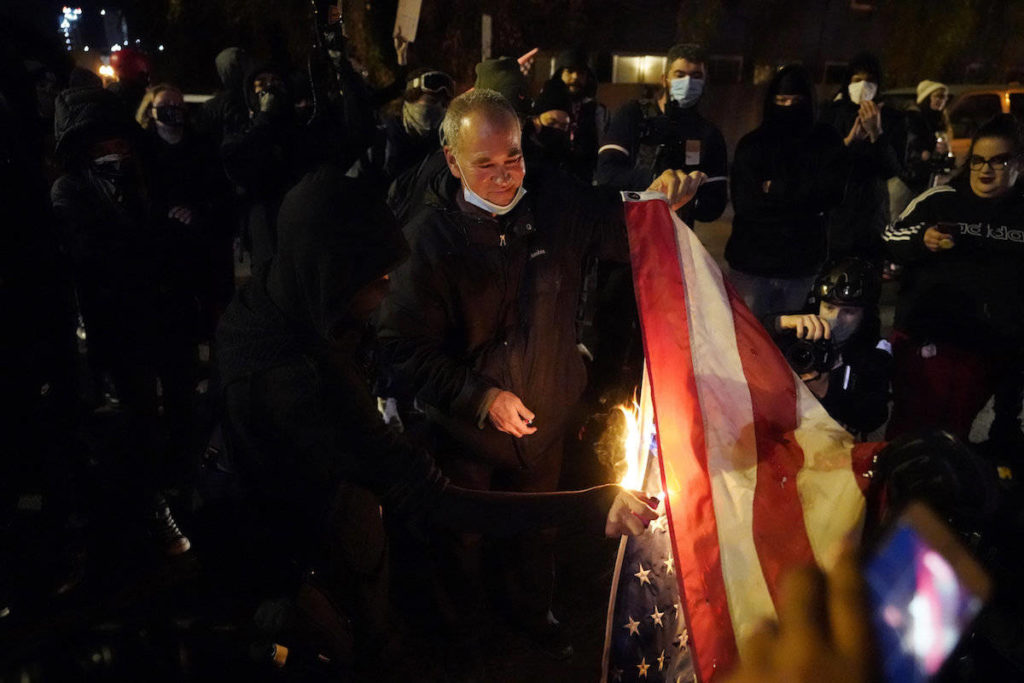 A U.S. flag is burned during a demonstration in the aftermath of the death of Kevin Peterson Jr., Saturday, Oct. 31, 2020, in Vancouver, Wash. Peterson. (AP/Marcio Jose Sanchez)