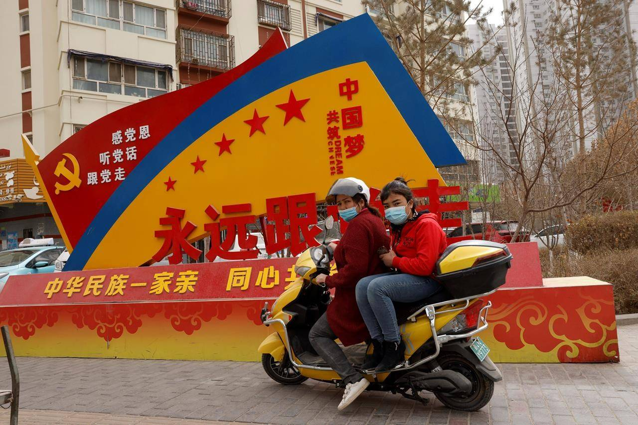 """FILE - In this March 19, 2021, file photo, residents wearing masks ride pass government propaganda with slogans some of which read """"Forever follow the Party"""" and """"China's Ethnicities One Family"""" in the city of Aksu in western China's Xinjiang region. A human rights group appealed to the United Nations on Monday, April 19, 2021 to investigate allegations China's government is committing crimes against humanity in the Xinjiang region. (AP Photo/Ng Han Guan, File)"""