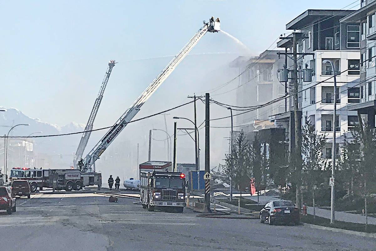 Fire crews continued to dowse a condo unit Tuesday morning after a massive overnight fire Monday, April 19, 2021. (Matthew Claxton/Langley Advance Times)
