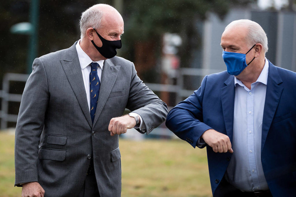 FILE – NDP Leader John Horgan, right, and local candidate Mike Farnworth greet one another with an elbow bump during a campaign stop in Coquitlam, B.C., on Friday, September 25, 2020. THE CANADIAN PRESS/Darryl Dyck