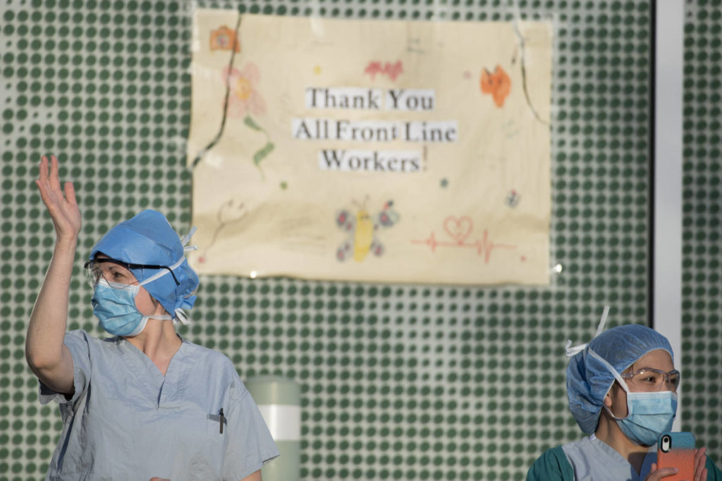 FILE – Health-care workers wave to people clapping and yelling thank you to the frontline workers during the 7 p.m.-tribute outside the Lions Gate Hospital in North Vancouver, B.C. Wednesday, April 8, 2020. THE CANADIAN PRESS/Jonathan Hayward