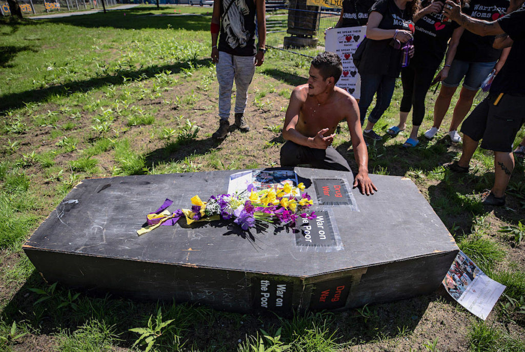 A man pauses at a coffin after carrying it during a memorial march to remember victims of overdose deaths in Vancouver. THE CANADIAN PRESS/Darryl Dyck