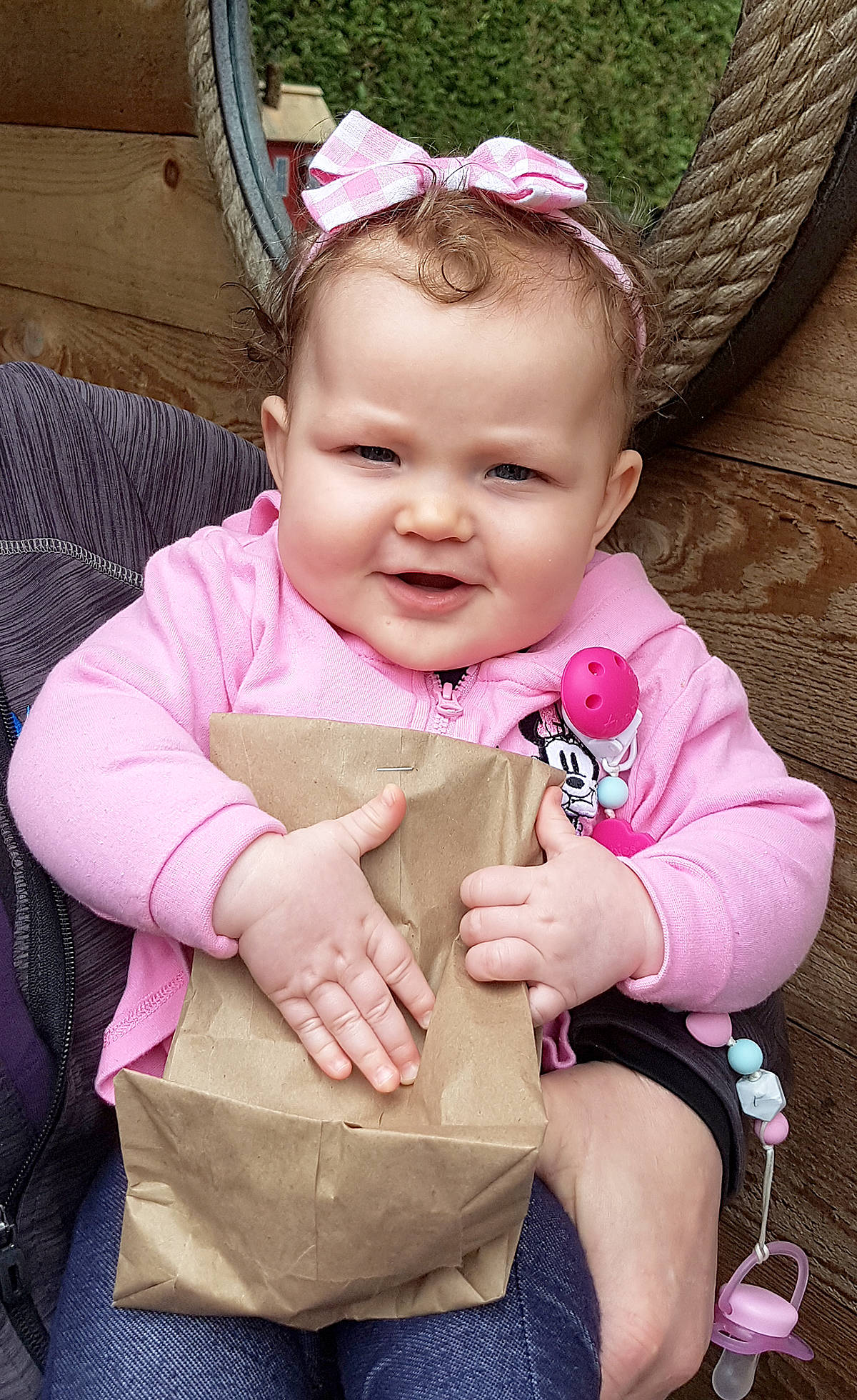 Young Emma, seven months old, held tight to her bag of lily bulbs picked out from Erikson's Daylily Gardens. (Pam Erikson/Special to Langley Advance Times)