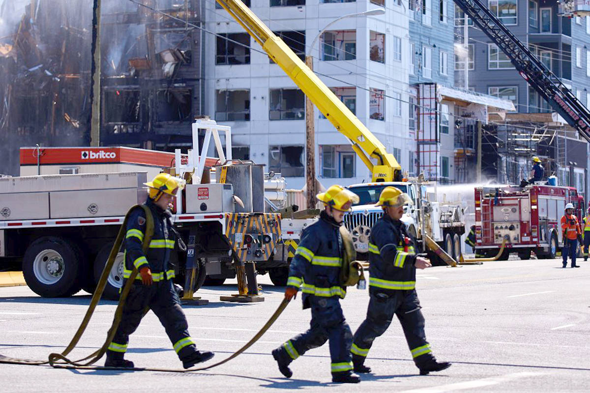 Firefighters carry equipment from the scene of Monday's Willoughby fire. The April 19, 2021 blaze turned the Alexander Square development at the corner of 208th Street and 80th Avenue to rubble. (Rob Wilton/Special to Langley Advance Times)
