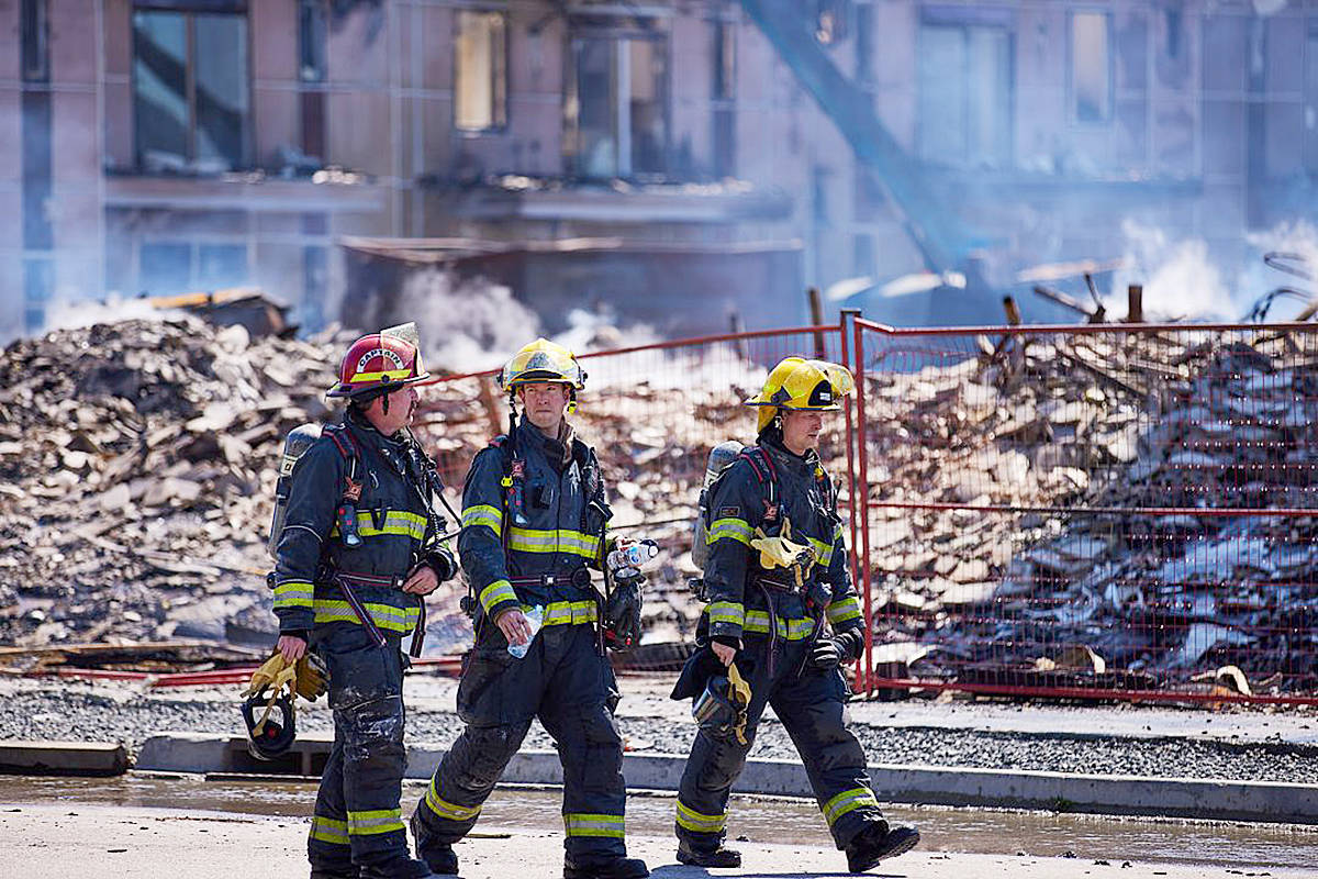 Firefighters walk past the rubble at the site of a construction site fire Tuesday, April 20 at 80th Avenue and 208th Street. (Rob Wilton/Special to the Langley Advance Times)