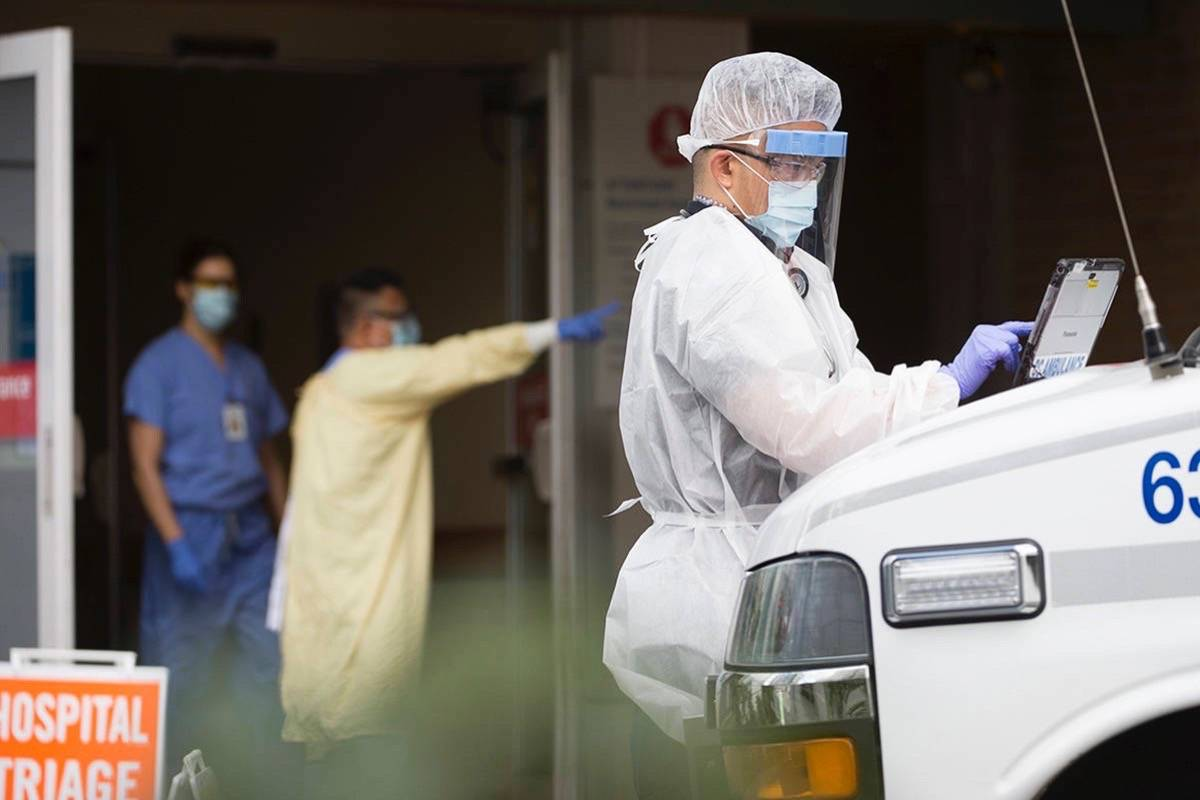 Ambulance paramedic in full protective gear works outside Lion's Gate Hospital, March 23, 2020. Hospitals are seeing record numbers of COVID-19 patients more than a year into the pandemic. (The Canadian Press)