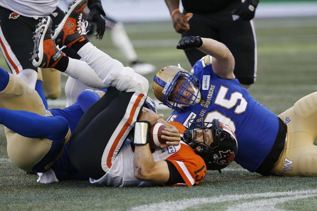 Winnipeg Blue Bombers' Craig Roh and Jake Thomas sack BC Lions quarterback Mike Reilly after he recovers his own fumble during CFL action in 2019. THE CANADIAN PRESS/John Woods