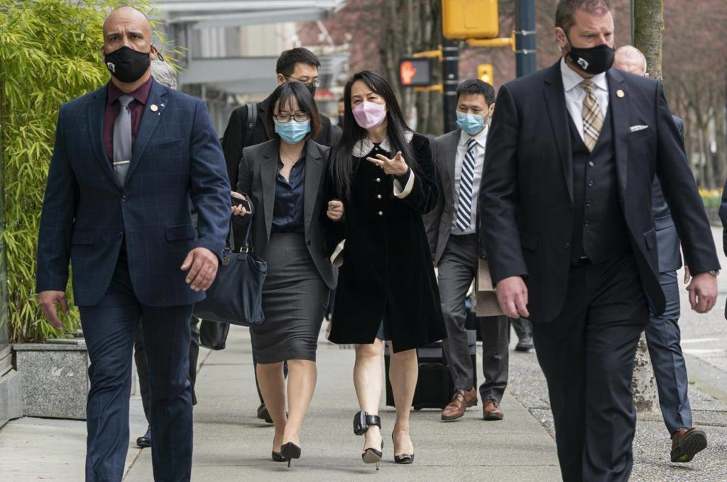 Meng Wanzhou, chief financial officer of Huawei, walks down the street with an acquaintance after leaving B.C. Supreme Court during a lunch break at her extradition hearing, in Vancouver, B.C., Thursday, April 1, 2021. A judge is scheduled to release her decision today on a request to delay the final leg of hearings in Meng Wanzhou's extradition case. THE CANADIAN PRESS/Rich Lam