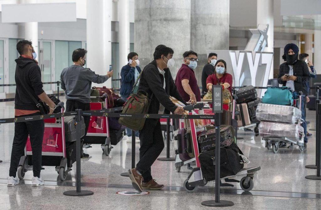 Passengers from Air India flight 187 from New Delhi wait for their transportation to quarantine after arriving at Pearson Airport in Toronto on Wednesday, April 21, 2021.THE CANADIAN PRESS/Frank Gunn