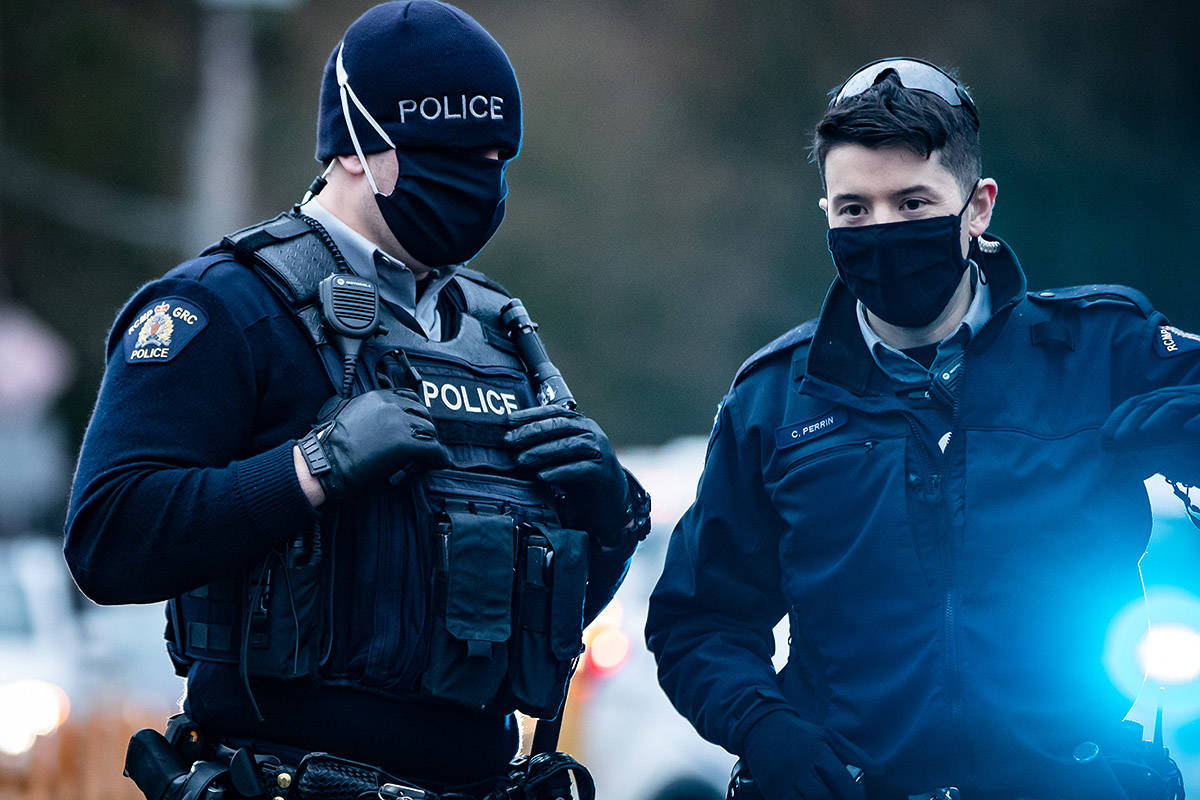 FILE – RCMP officers wearing face masks to curb the spread of COVID-19 stand by as protesters opposed to the Trans Mountain pipeline expansion block rail lines, in Burnaby, B.C., on Friday, November 27, 2020. THE CANADIAN PRESS/Darryl Dyck