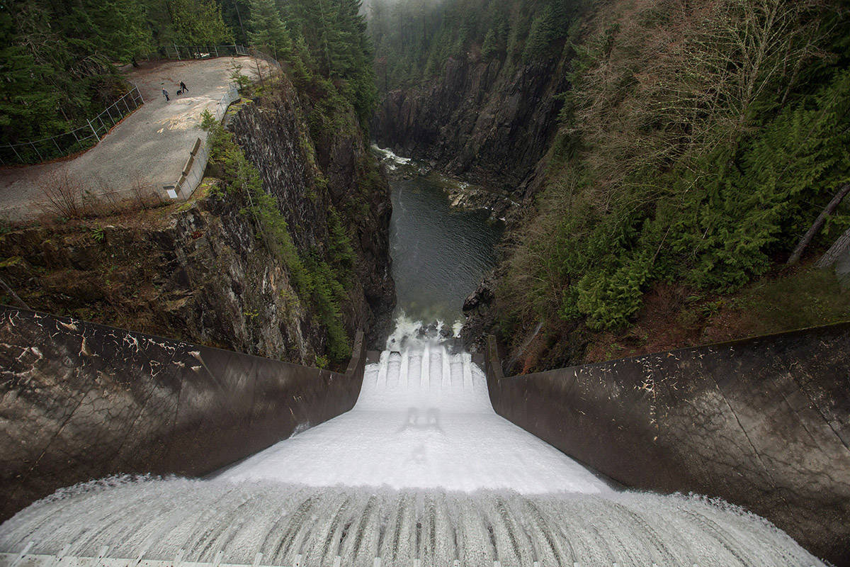 FILE – Water flows over the Cleveland Dam as people walk with a dog in Cleveland Park in North Vancouver, B.C., on Christmas Day, Friday Dec. 25, 2015. THE CANADIAN PRESS/Darryl Dyck