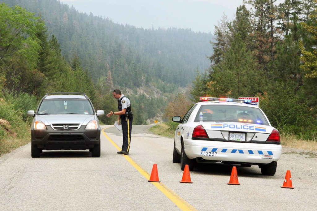 RCMP Constable Etsell speaks to tourists leaving the area at a police roadblock on Westside Road south of Fintry, B.C., Thursday, July 23, 2009. THE CANADIAN PRESS/ Yvonne Berg