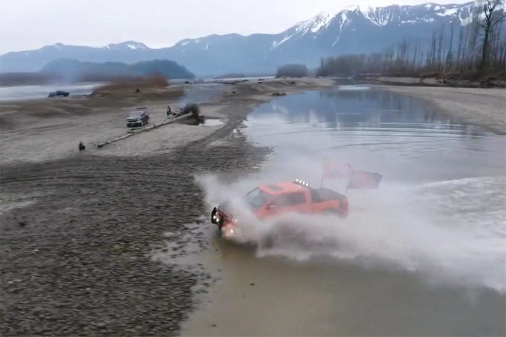 Screenshot from a video posted in early 2021 showing repeated crossings of side channels by trucks on the Fraser River near Chilliwack. (Facebook)