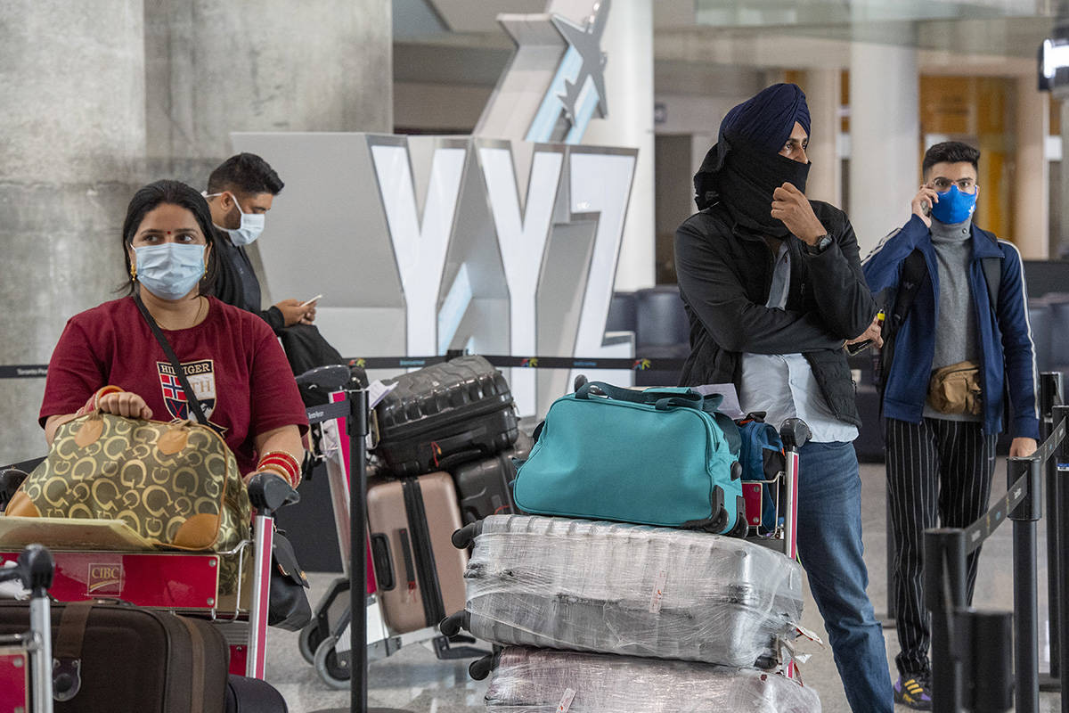 Passengers from Air India flight 187 from New Delhi wait for their transportation to quarantine after arriving at Pearson Airport in Toronto on Wednesday, April 21, 2021. THE CANADIAN PRESS/Frank Gunn