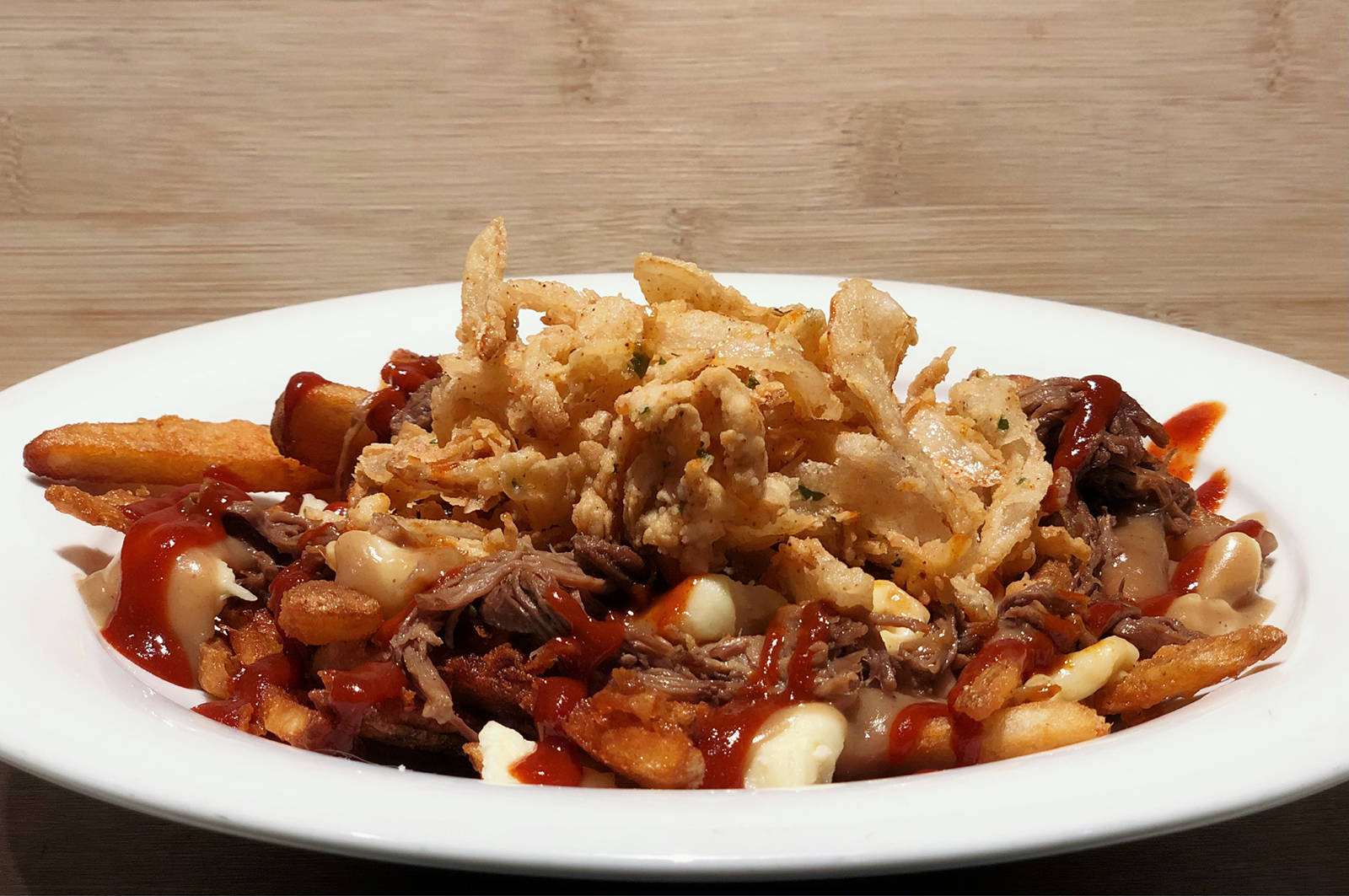 Darcy's Pub Westshore offers its BBQ Brisket Poutine – crispy beer battered fries, real cheese curds, house-made brisket gravy, and 12-hour braised shredded beef brisket, topped with a spicy barbecue drizzle and fried buttermilk onions.