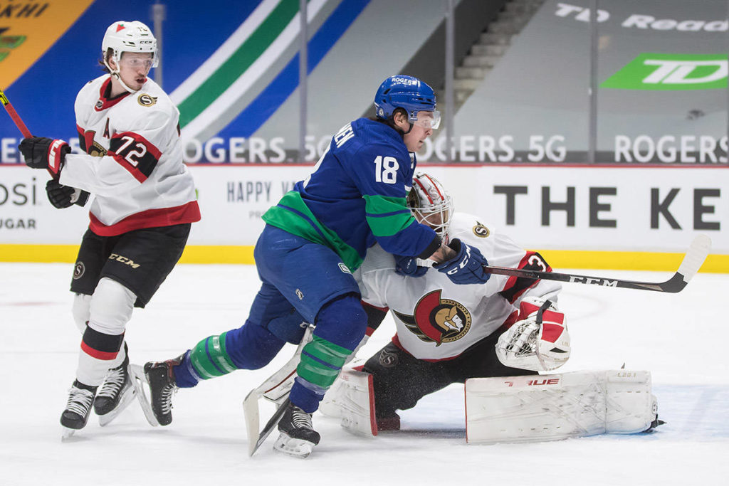 Vancouver Canucks' Jake Virtanen (18) is tripped by Ottawa Senators goalie Matt Murray as Thomas Chabot (72) watches during the second period of an NHL hockey game in Vancouver, on Saturday, April 24, 2021. THE CANADIAN PRESS/Darryl Dyck