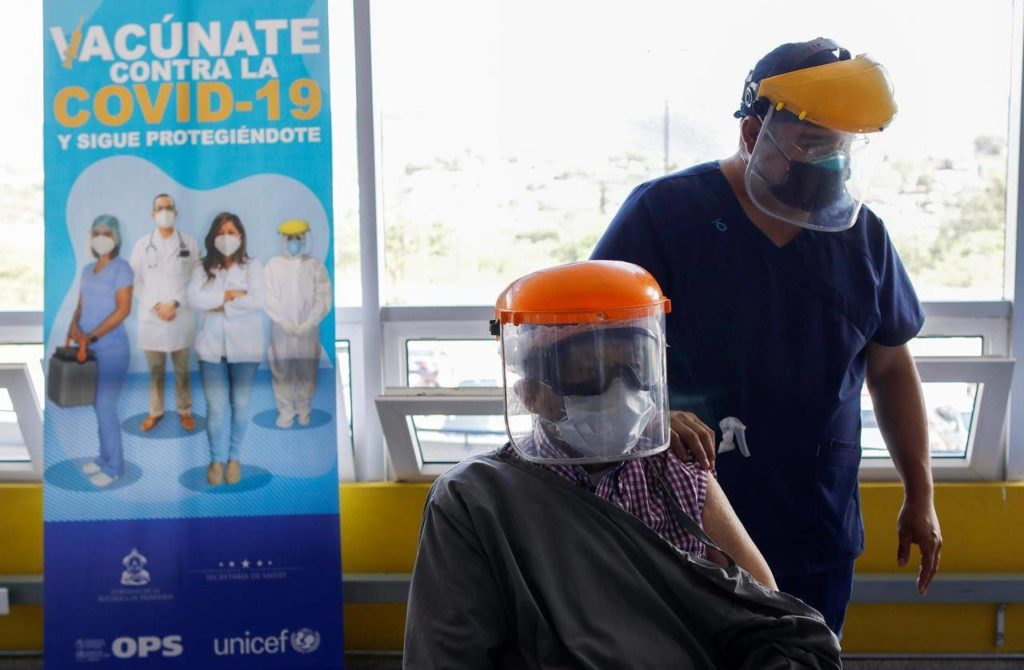 Roberto Maradiaga, 70, a retired doctor, is helped by his son Luis Roberto, while he waits for the Russian COVID-19 vaccine Sputnik V, as part of a vaccination campaign in Tegucigalpa, Honduras, Friday, April 23, 2021. Honduras has obtained a paltry 59,000 vaccine doses for its 10 million people. Similar gaps in vaccine access are found across Africa, where just 36 million doses have been acquired for the continent's 1.3 billion people, as well as in parts of Asia. (AP Photo/Elmer Martinez)