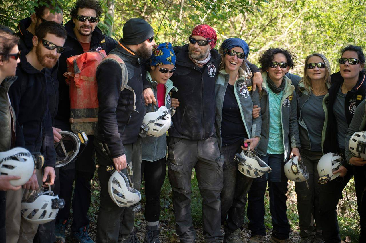 """Members of the French team that participated in the """"Deep Time"""" study pose for a photo after exiting the Lombrives Cave in Ussat les Bains, France, Saturday, April 24, 2021. After 40 days in voluntary isolation, 15 people participating in a scientific experiment have emerged from a vast cave in southwestern France. Eight men and seven women lived in the dark, damp depths of the Lombrives cave in the Pyrenees to help researchers understand how people adapt to drastic changes in living conditions and environments. They had no clocks, no sunlight and no contact with the world above. (AP Photo/Renata Brito)"""