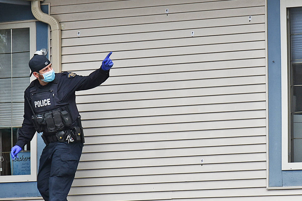 A RCMP officer marks bullet holes in a home that Mounties say was wrongly targeted in the 18800-block of 122nd Avenue in Pitt Meadows Monday morning, April 26, 2021. (Neil Corbett/The News)