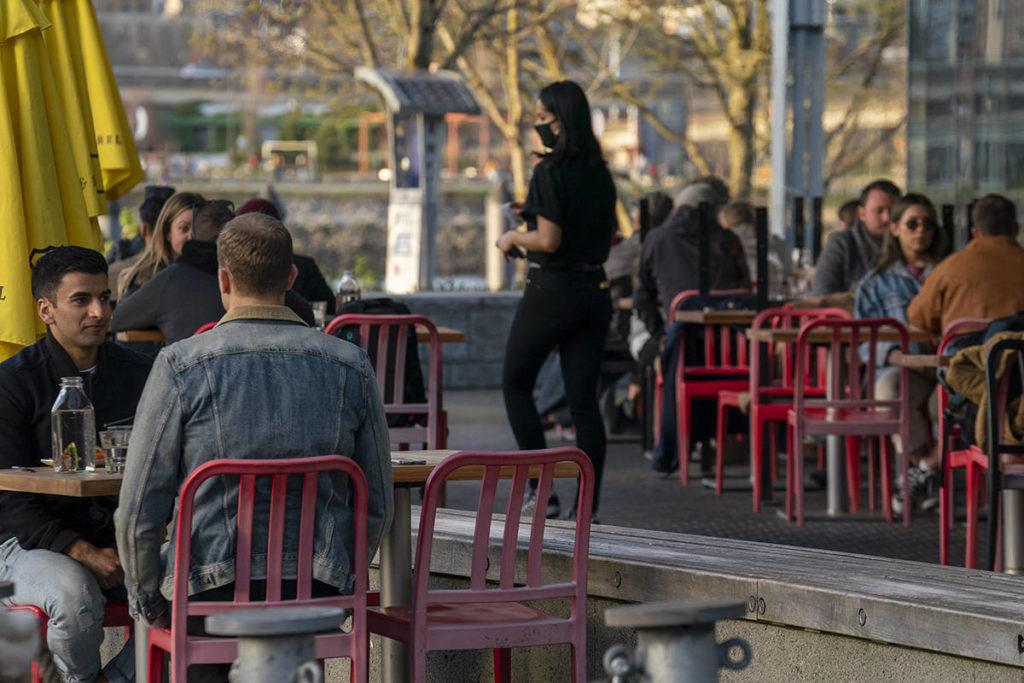 Restaurant patrons enjoy the weather on a patio in Vancouver, B.C., Monday, April 5, 2021. The province has restricted indoor dining at all restaurants in B.C. due to a spike in COVID-19 numbers. THE CANADIAN PRESS/Jonathan Hayward
