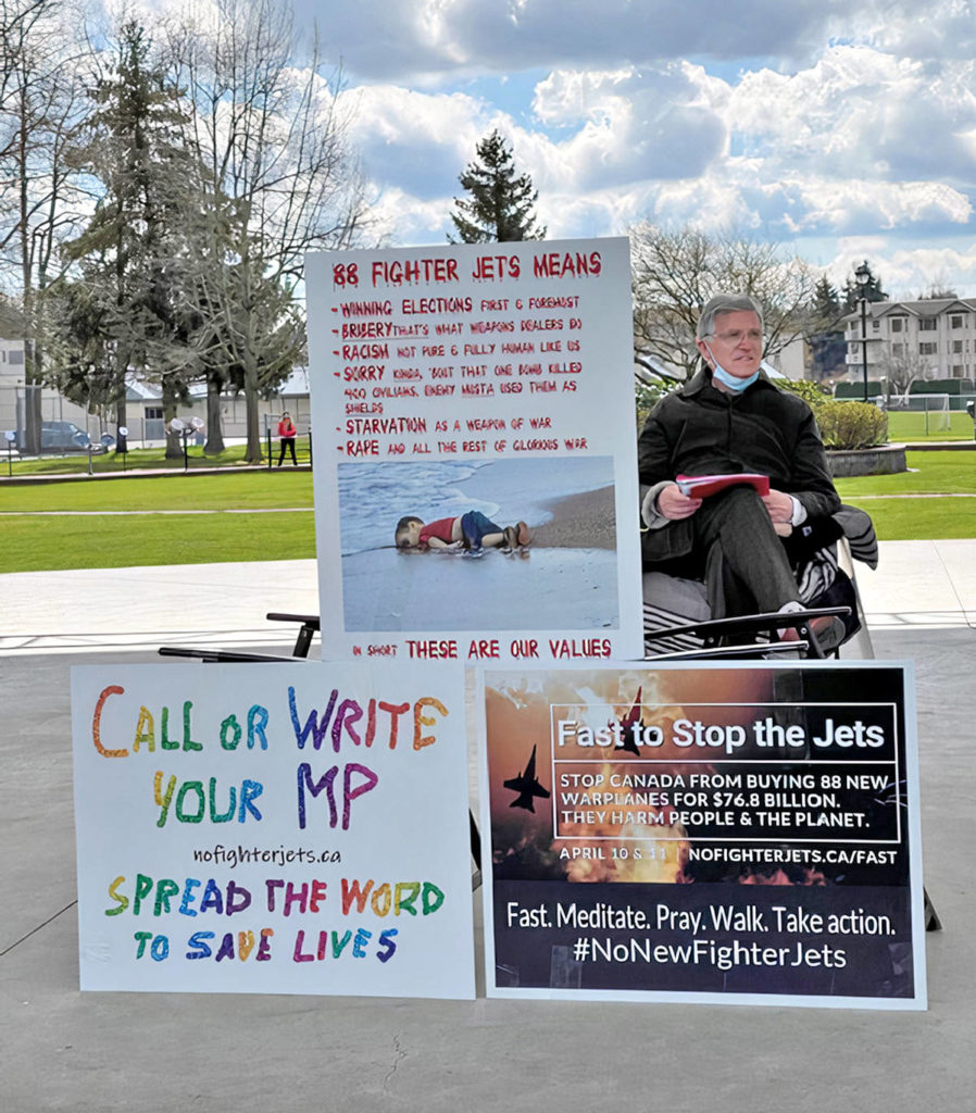 For the first seven days of his protest fast, Langley doctor Brendan Martin spent six hours every day in Langley City's Douglas Park with protest signs. He was part of a cross-Canada campaign against fighter jet funding (Special to Langley Advance Times)