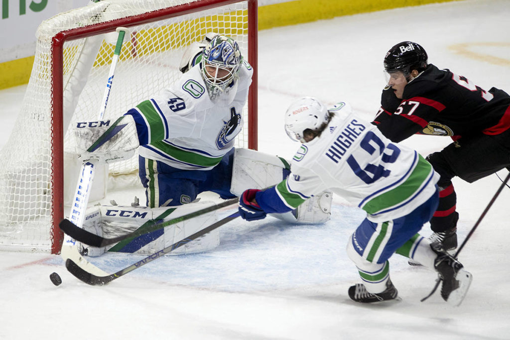 Vancouver Canucks goaltender Braden Holtby defects the puck wide of the net as defenceman Quinn Hughes and Ottawa Senators centre Shane Pinto give chase during second period NHL action in Ottawa, Monday, April 26, 2021. THE CANADIAN PRESS/Adrian Wyld