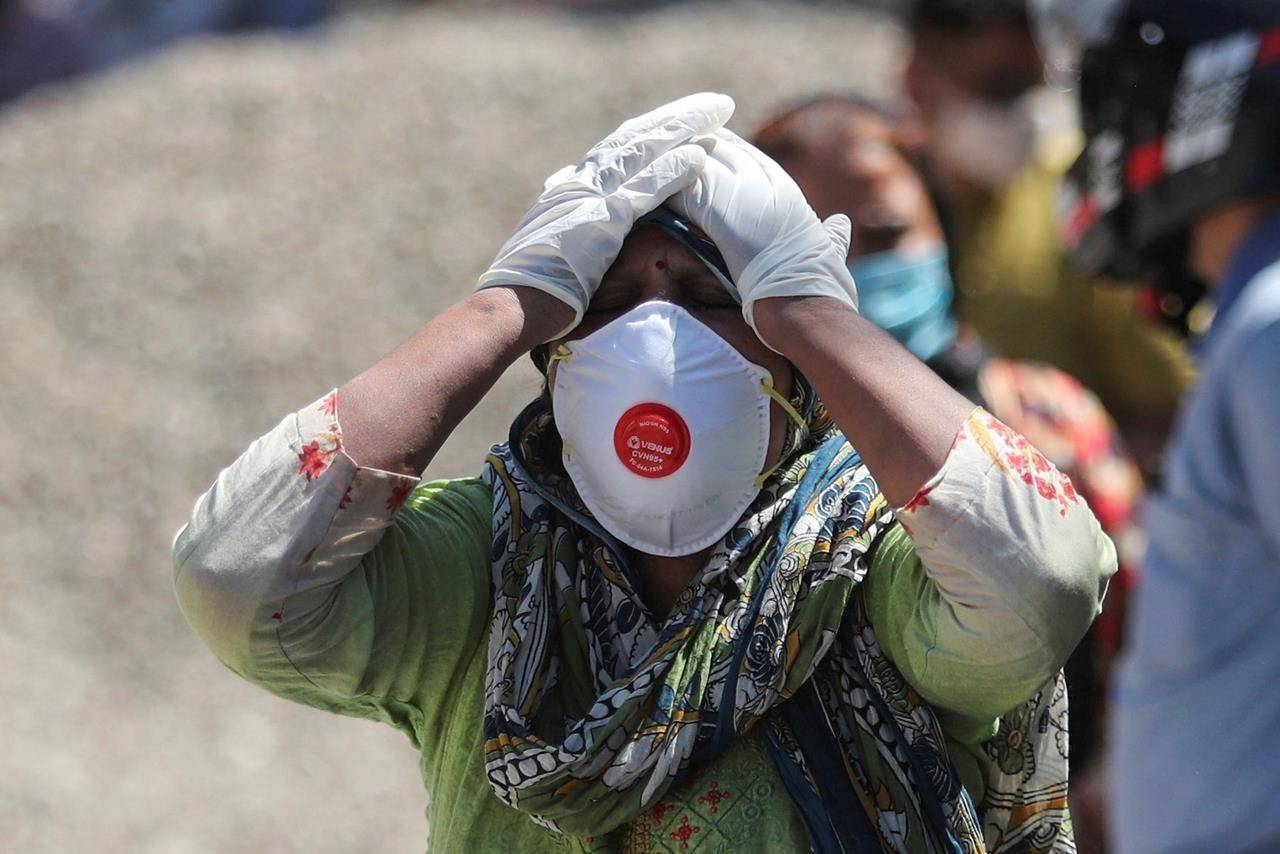A relative of a person who died of COVID-19 reacts at a crematorium in Jammu, India, Sunday, April.25, 2021. THE CANADIAN PRESS/AP/Channi Anand