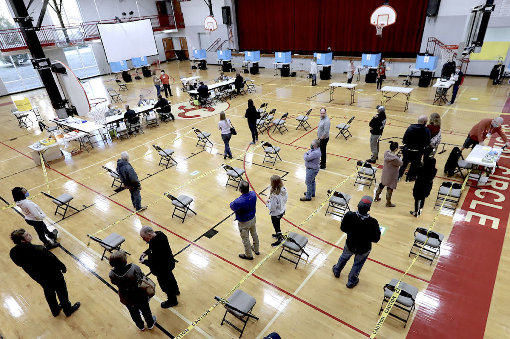 Voters socially distance while waiting in line. (Curtis Compton/AP)