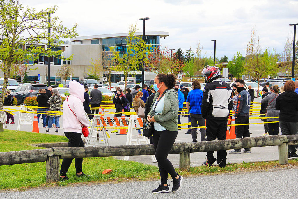 """A woman walks past a long lineup that snaked through the parking lot at the Cloverdale Rec. Centre April 27 after Fraser Health allowed people age 30 and over from """"high-transmission neighbourhoods"""" to access the AstraZeneca shot. The temporary vaccination centre is located on the Cloverdale Fairgrounds. (Photo: Malin Jordan)"""