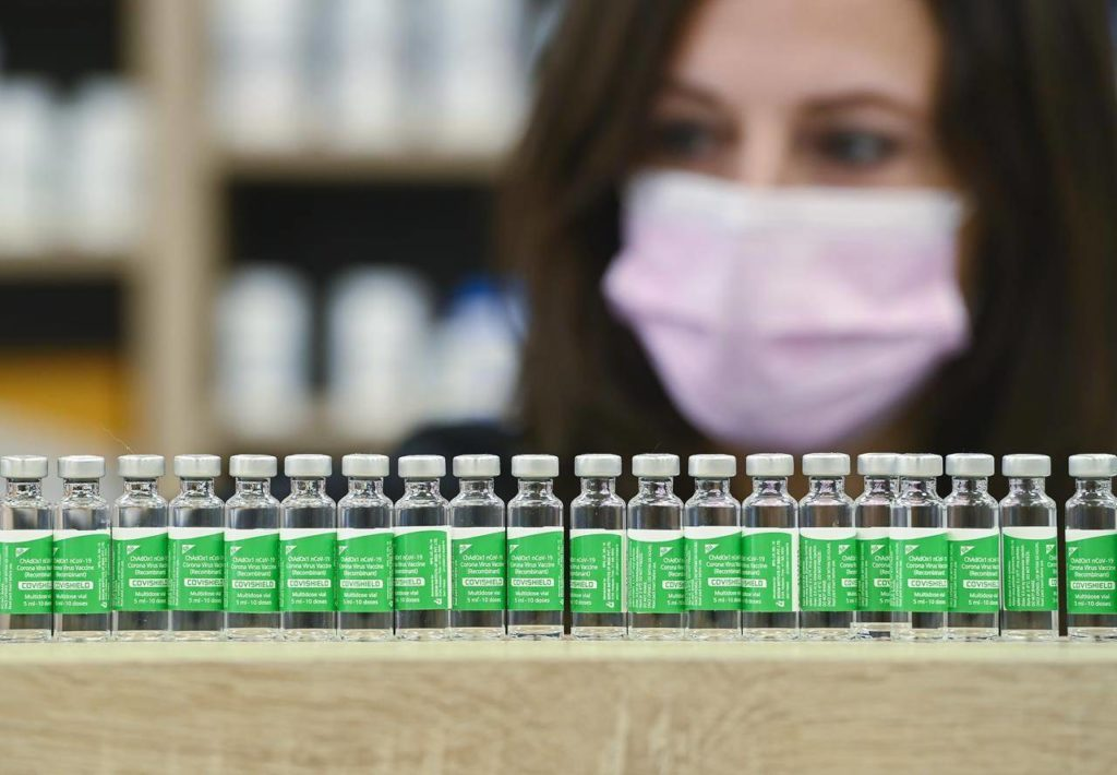 Pharmacist Barbara Violo arranges empty vials of the Oxford-AstraZeneca COVID-19 vaccine that she has provided to customers at the Junction Chemist, an independent pharmacy in Toronto, Monday, April 19, 2021. THE CANADIAN PRESS/Nathan Denette