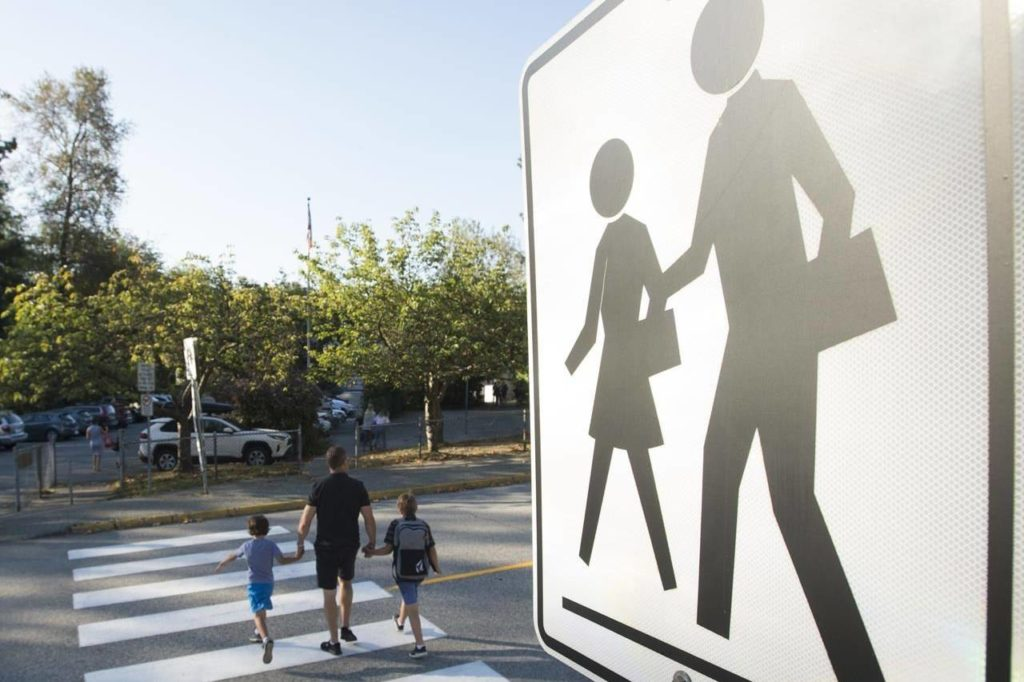 Children walk with their parents to Sherwood Park Elementary in North Vancouver for the first day back to school, Thursday, Sept. 10, 2020. THE CANADIAN PRESS/Jonathan Hayward