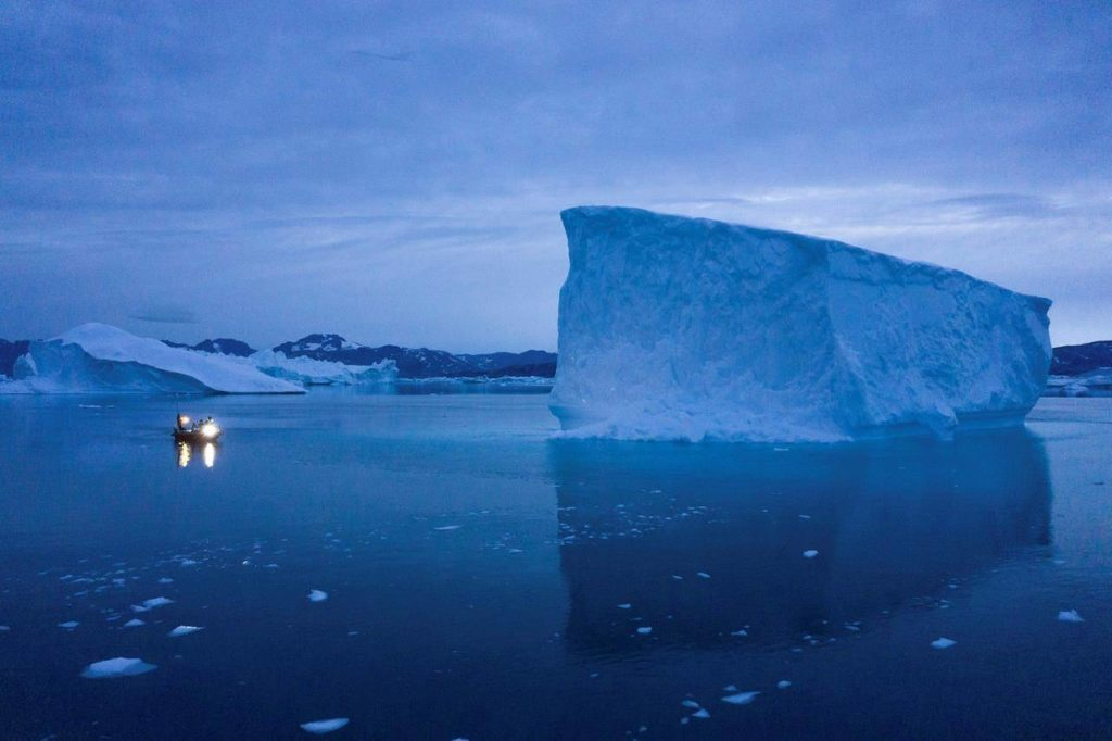 A boat navigates at night next to large icebergs in eastern Greenland. Greenland's ice has been melting for more than 20 years. THE CANADIAN PRESS/Felipe Dana