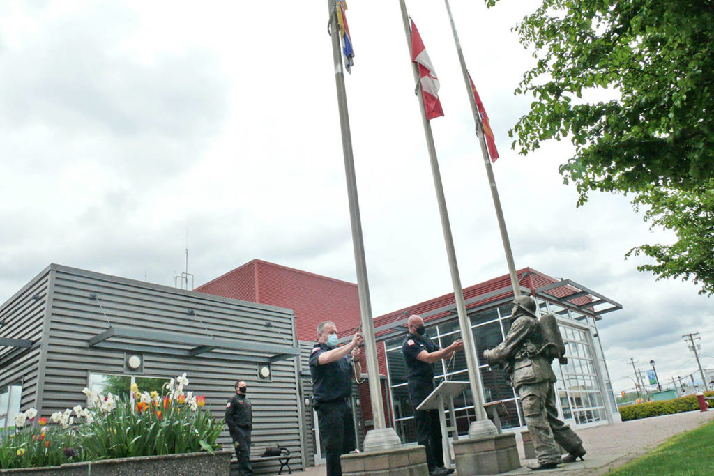 As a statue of a firefighter in full turnout gear looked on at the Langley City fire hall, firefighters lowered flags to half-mast on Wednesday, April 28, to mark the National Day of Mourning for workers killed, injured or made ill by their job (Dan Ferguson/Langley Advance Times)