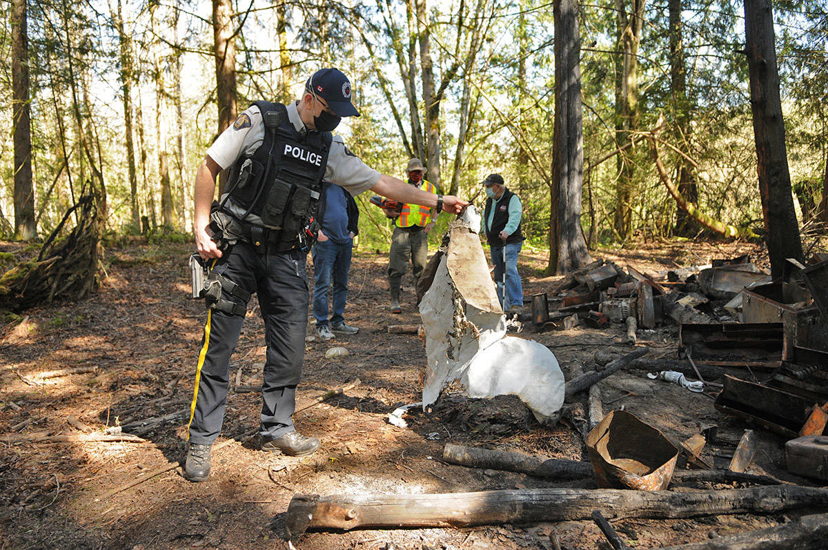 Const. Marc Verreault holds up a tarp likely used as part of a wall for the makeshift homeless structure which caught fire on April 9, 2021. (Jenna Hauck/ Chilliwack Progress)