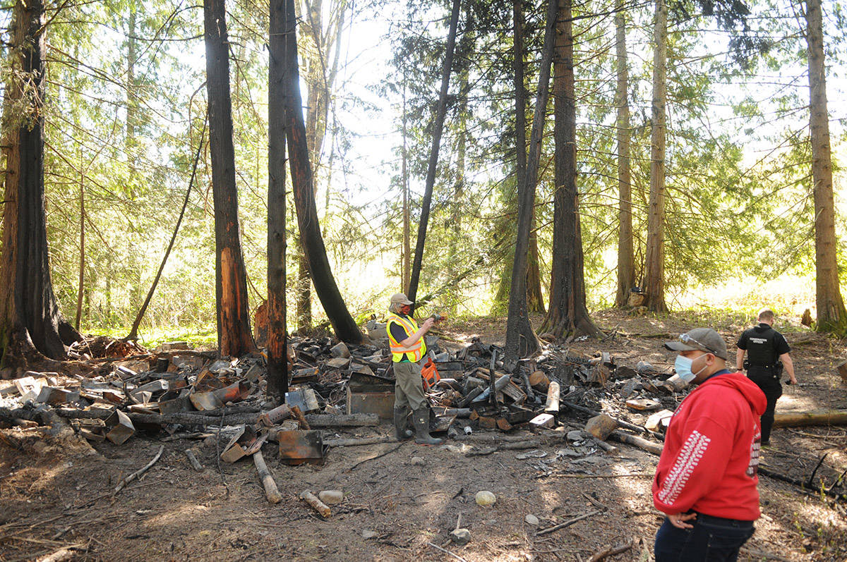 Volunteers, a conservation officer and an RCMP officer visit the burnt homeless camp on April 15, 2021. (Jenna Hauck/ Chilliwack Progress)