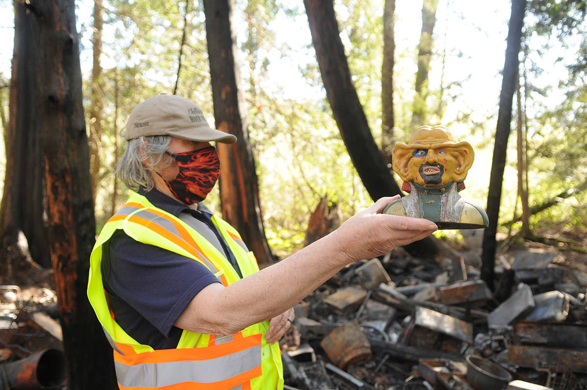 Chris Gadsden holds up a Star Trek 'Quark' figure head – one of the few items not burned in a homeless camp fire in the Chilliwack River Valley. (Jenna Hauck/ Chilliwack Progress)