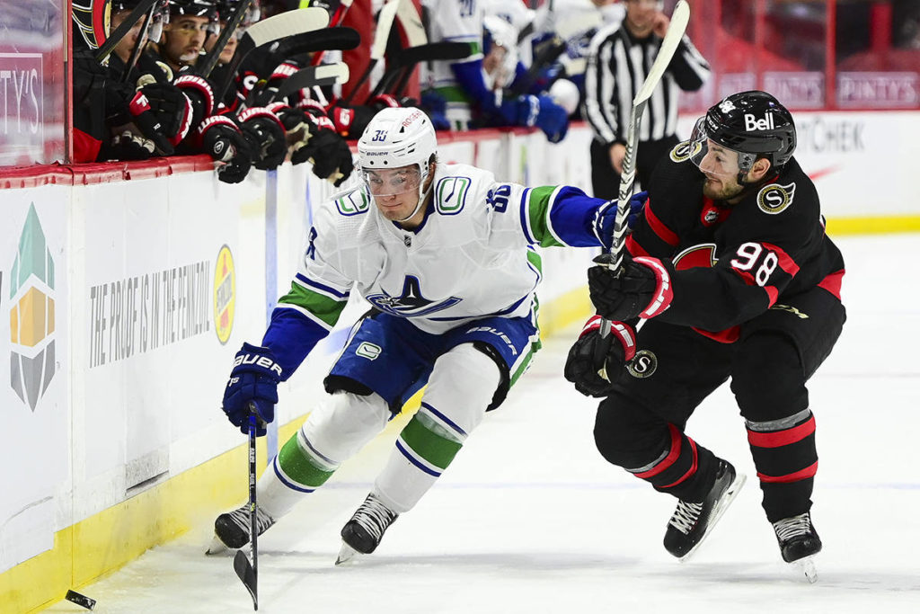 Vancouver Canucks' Nils Hoglander, left, and Ottawa Senators' Victor Mete battle for the puck during first period NHL action in Ottawa on Wednesday, April 28, 2021. THE CANADIAN PRESS/Sean Kilpatrick