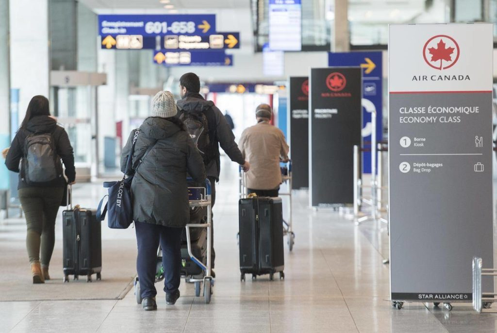 Airline passengers walk by a check-in desk at Trudeau International Airport in Montreal, Friday, March 20, 2020. THE CANADIAN PRESS/Graham Hughes